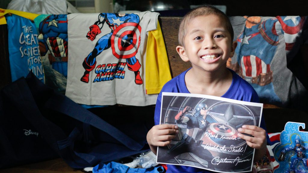Wish Kid Xander posing with his gifts from Disney Philippines